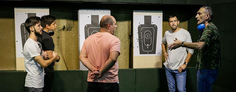 profesor y alumnos de la escuela de seguridad privada en galería de tiro